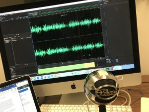 A behind the scenes look of recording my podcast, on an iMac, using a blue snowball mic, and having my macbook with an outline