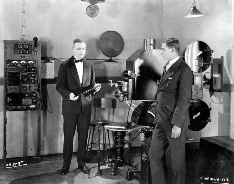 Two men showing how to use the VITAPHONE film sound system